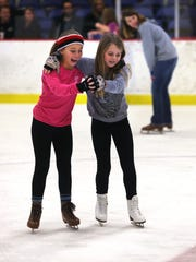 Anna Spellacy (left), 9, and Katelyn Hedrick, 10, try their hand at skated dancing at the Indiana State Fairgrounds' new Youth Arena ice skating rink.