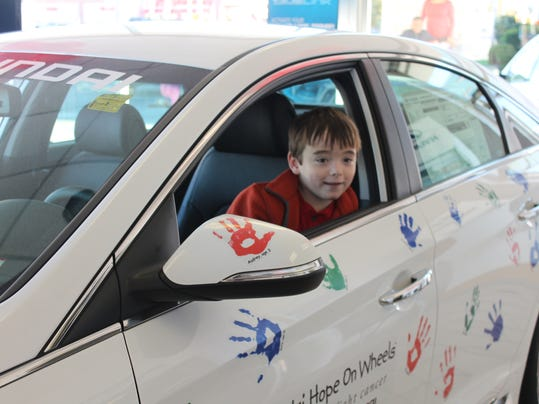 Mason Smith poses in the Hope on Wheels Car, the vehicle in which he rode during the Hanover Halloween parade.