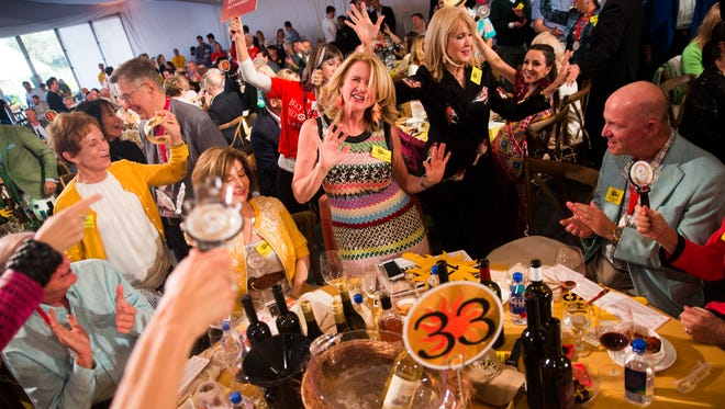 "Ann Welsh McMulty dances after winning Lot 54 after bidding $220,000 during the 2017 ""Bright Sunshiny Day"" Auction at the Naples Winter Wine Festival on Saturday, January 28, 2017, at the The Ritz-Carlton Golf Resort in North Naples. Lot 54, ""Say Hi To Heidi,"" included VIP access to the finale of the show ""Project Runway."""