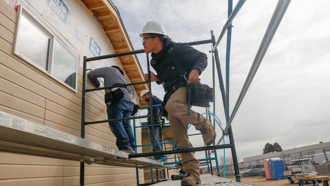 Jamane Benallie works on a home with classmates on Wednesday at the San Juan College School of Trades and Technology in Farmington.