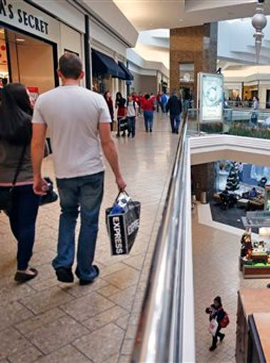 In this Nov. 29, 2013 file photo, shoppers walk through Cherry Creek Mall, in Denver. Consumer spending in June rose by the smallest amount in four months as shoppers cut back on purchases of cars and other big-ticket items. The Commerce Department says consumer spending edged up 0.2 percent in June, the poorest showing since a similar increase in February.