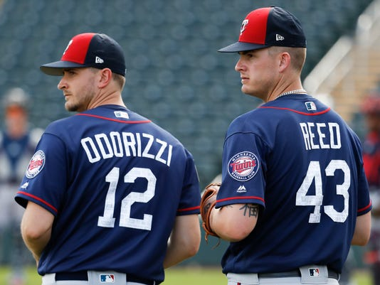 FILE - In this Feb. 21, 2018, file photo Minnesota Twins relief pitcher Addison Reed (43) and pitcher Jake Odorizzi (12) watch their teammates practice during spring training baseball in Fort Myers, Fla. The Twins were already on the upswing after reaching the AL wild card game last year behind a lot of young talent. They took another major step forward this offseason with a series of low-risk upgrades to the bullpen, the rotation and the lineup with the potential for a big payoff. (AP Photo/John Minchillo, File)