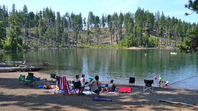 People sit on the shores of Scout Lake, just northeast of Suttle Lake in the Deschutes National Forest. People sit on the shores of Scout Lake, just northeast of Suttle Lake in the Deschutes National Forest.