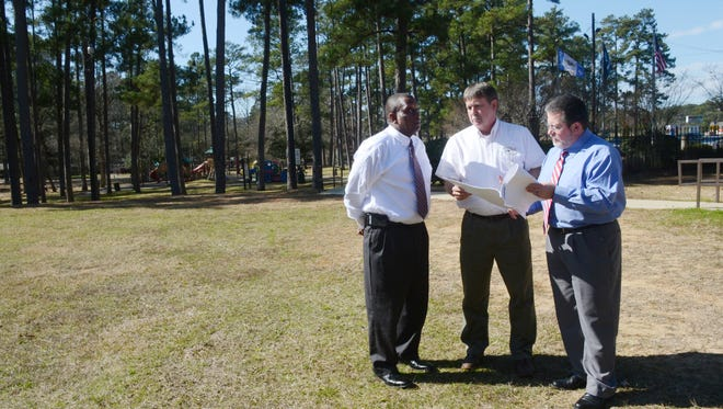Pineville Mayor Clarence Fields (left), public works director Charlie Moore and Rich Dupree, chief of staff look over plans for a splash pad that is going to be built at Kees Park in Pineville.