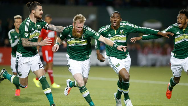 Portland Timbers defender Nat Borchers, second from left, celebrates with teammates after heading a ball for a goal against FC Dallas during an MLS soccer game Saturday, April 4, 2015, in Portland, Ore.