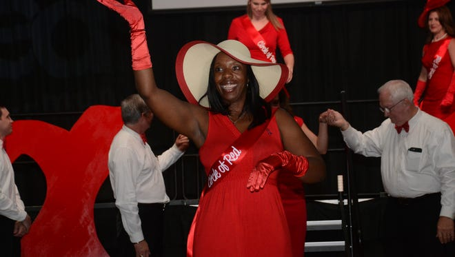 Sharifa Baker Bevels waves after she and other members of the Circle of Red are introduced at the 2015 Central Louisiana Go Red for Women luncheon.