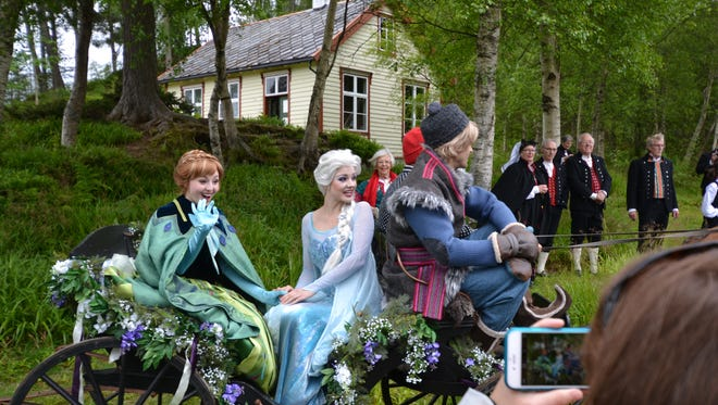 The characters Anna and Elsa from the animated Disney film 'Frozen' arrive at a summer celebration organized for passengers of the Disney Magic during a port stop in Alesund, Norway.
