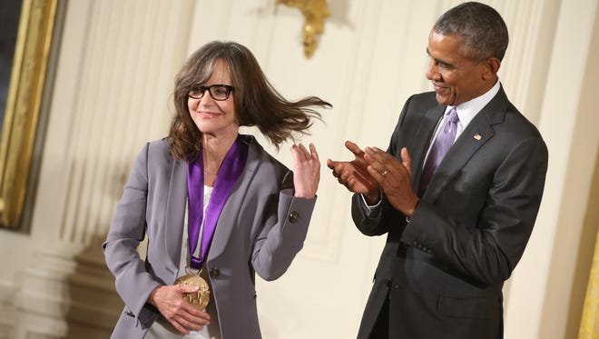 President Obama applauds actress Sally Field after presenting her with the 2014 National Medal of Arts.