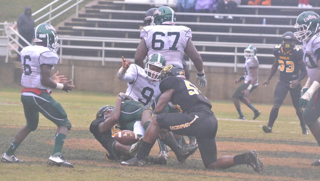 Mississippi Valley's Rubin Thurston is brought down by the Grambling defense as the ball slips away on a wet Saturday in Grambling, Louisiana.