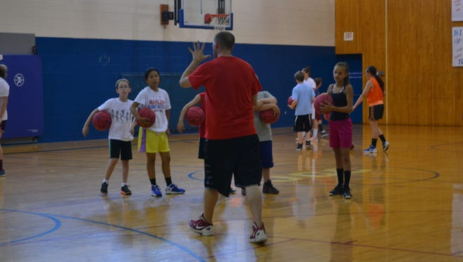 Students are being instructed in preparation for a drill during a JCC Youth Hoopsters session.