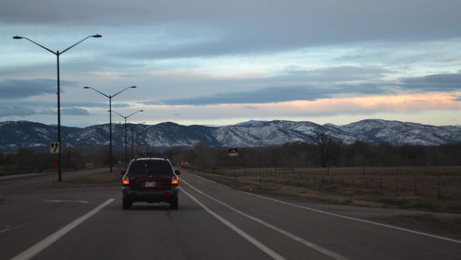 Prospect Road is all clear Tuesday morning while the sun bounces off clouds over a dusting of snow in the foothills.