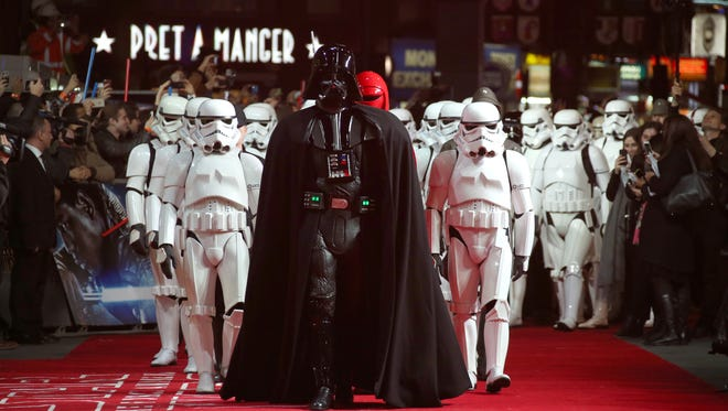 People dressed as stormtroopers and Darth Vader walk on the red carpet upon arrival at the European premiere of the film 'Star Wars: The Force Awakens ' in London on Wednesday.