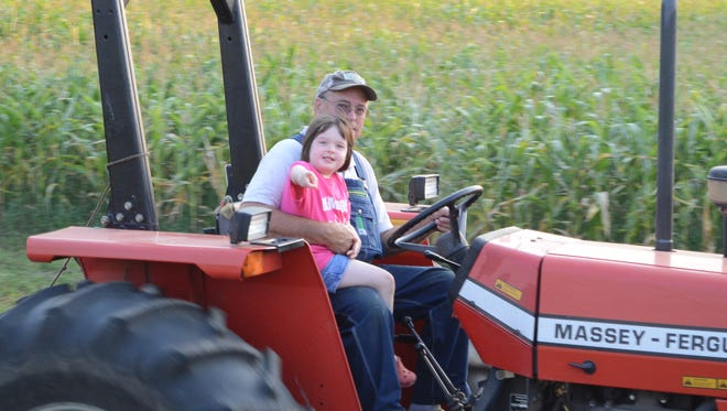 Lung transplant recipient Sid Whitaker, 66, of Hart gives his granddaughter a ride on his tractor.