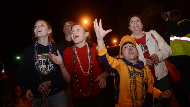 "Hilary Harlow (left), Olivia Hunter, her brother Ian Hunter and mom Shannon Chiasson scream for beads as the first ""Light the Night"" Mardi Gras parade rolls into Alexandria from Pineville last year."