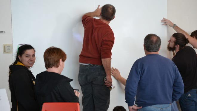 Emerging Technology Ventures Inc., OteroStem members and Alamogordo High School students install long white boards at the high school for the school's robotics teams.