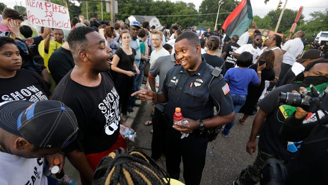 Memphis Police Lt. A. Gardner, center right, tries to calm a crowd, including Antonio Blair, center left, as members of the community attempt to protest during Graceland's Elvis Presley Candlelight Vigil Aug. 15, 2016.