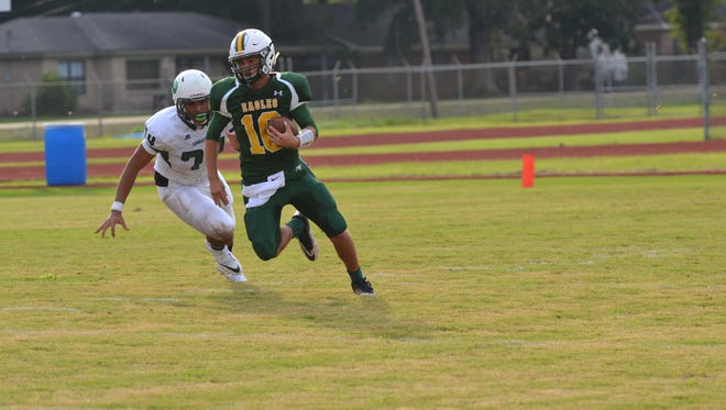 Menard quarterback John Roy (10) looks for running room with Peabody defender Wayne Compton Jr. (74) in hot pursuit in the first game of the Cenla Jamboree Friday, Aug. 26, at Alexandria Senior High. Peabody won the game 28-7.