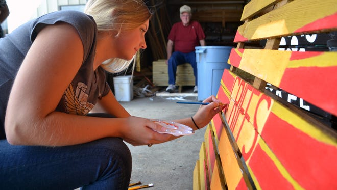 Ashley rice, a senior at Crescent High School, paints a sign for Griffs store in Iva for the Iva Depot Day.