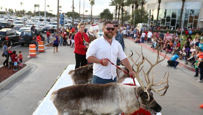 Robert O'Neil holds onto Dasher as he rides Santa Claus' sleigh during the Santa Parade at La Palmera mall on Thursday, Nov. 3, 2016.