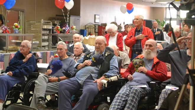 Residents in the Richard M. Campbell Veterans Nursing Home salute or place their hands over their hearts as taps plays during a ceremony.