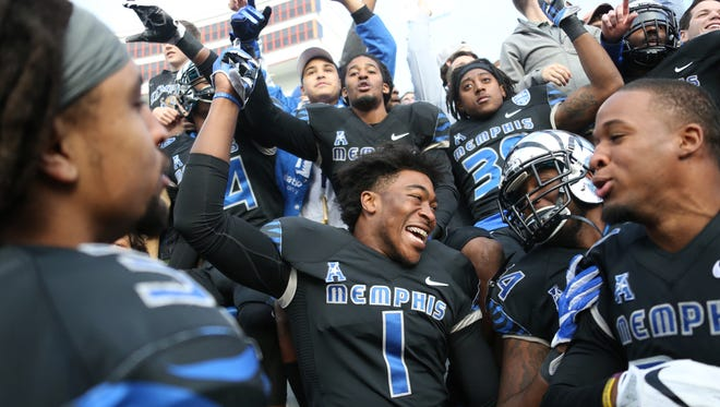 Memphis defensive lineman Jacoby Hill (1) celebrates with teammates at the conclusion of an NCAA college football game Friday, Nov. 25, 2016, in Memphis, Tenn. Memphis defeated Houston 48-44. (AP Photo/Nikki Boertman)