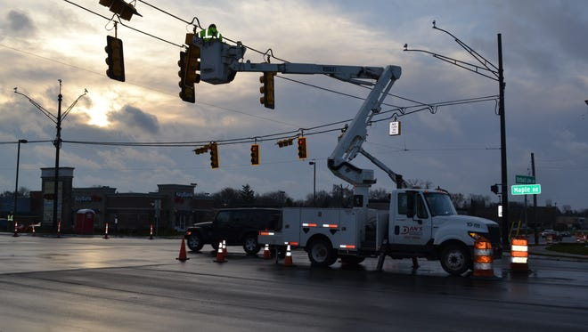 Workers complete work on traffic signals as the repaving and widening of the intersection of Maple and Orchard Lake roads wraps up.