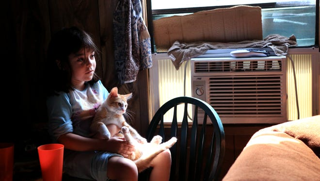 Zelimah Niles, 6, holds her cat Yeyo and sits next to the air conditioner while watching television in her home in a colonia south of London on Thursday, July 7, 2016. She and her brother don't get to play outside unless they go to town and visit a playground because of mosquitoes around their home and the fear of Zika.