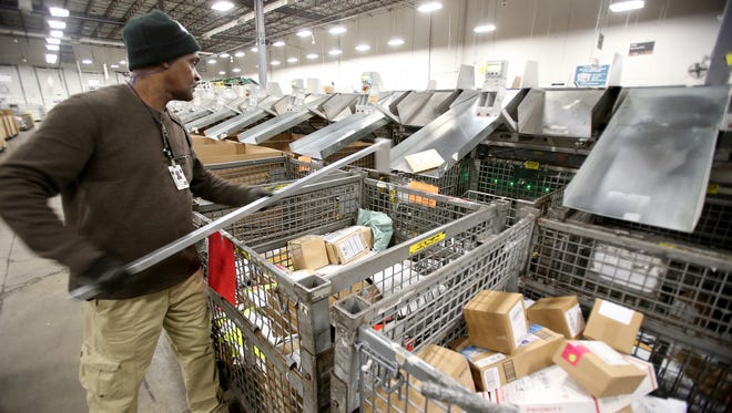 Larry Wilson, parcel post distribution clerk, helps packages into the appropriate destination bin at the USPS Jet Cove processing and distribution center.