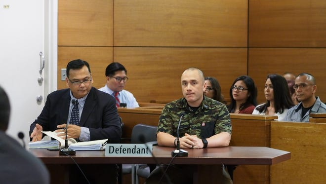 In this Dec. 15, 2016 file photo, former Guam police officer Mark Torre Jr., right, attends a pre-trial hearing in the Superior Court of Guam. Torre was back in court Wednesday Aug. 2, 2017, for a restitution hearing.