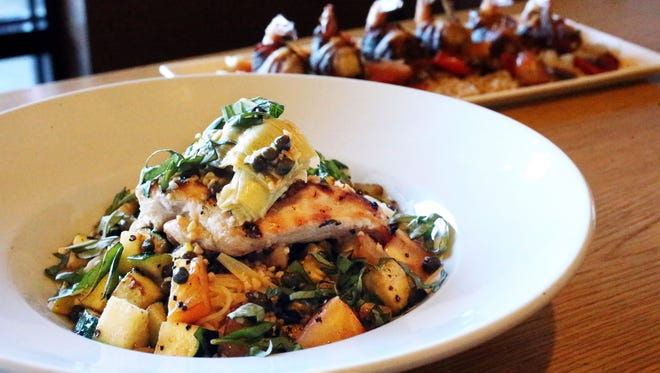 Chicken Piccata, foreground is a dish from Fuzion Casual Fine Dining at 134380 Edgemere, Suite 103 near El Dorado High School. The dish includes grilled chicken breast with a lemon caper sauce served over capellini pasta and fresh vegetables.