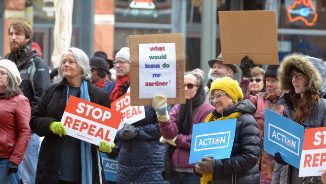 People rally to protect the Affordable Care Act, Medicaid, Medicare and Planned Parenthood at Old Town Square on Sunday, Jan. 15, 2017.