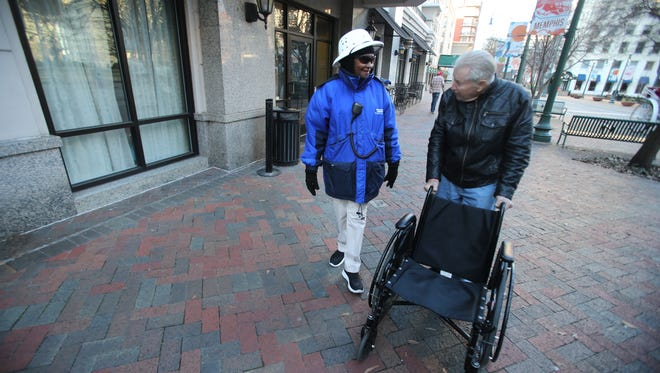 Johnnie Willis, who has worked the Blue Suede Brigade for more than 12 years, walks along Main Street with Lanny Merrill. The Downtown Memphis Commission will partner with the Workforce Investment Network to hold two job fairs in mid-February to hire for newly created, full-time positions paying living wages.