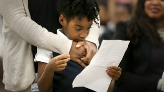 Dunbar Elementary kindergarten student Genesis Collins looks over her notes supporting before taking the microphone to speak on behalf of Dunbar during the public comment portion of the Shelby County Schools board meeting.