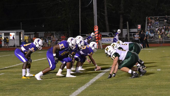 The ASH Trojans (purple) and Menard Eagles (green and white) square off in the second game of the ASH Jamboree Friday night at Butch Stoker Field. ASH defeated Menard 29-0.