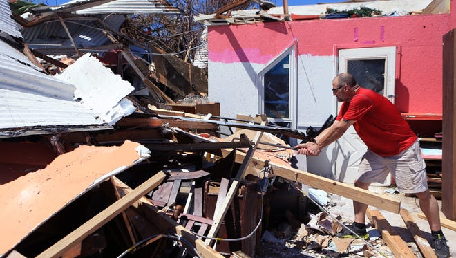 """Lance Esswein digs through the rubble of his wife's antique and resale shop in Rockport, Texas on Aug. 29, 2017. The shop was flattened by Hurricane Harvey. """"My wife's dream is in this shop,"""" he said."""