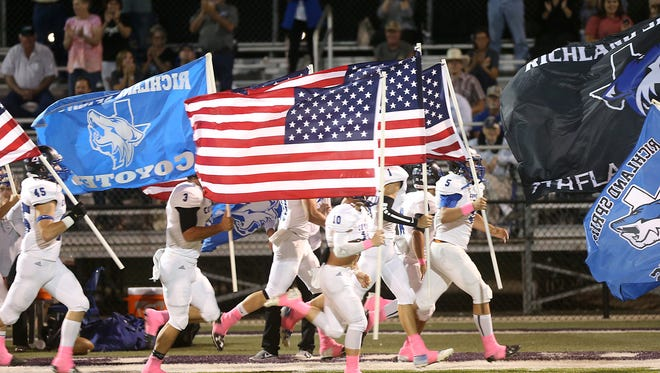 The Richland Springs Coyotes run onto the field waving the American flag and team flag at Friday night's game against the Sterling City Eagles, Oct. 6, 2017.