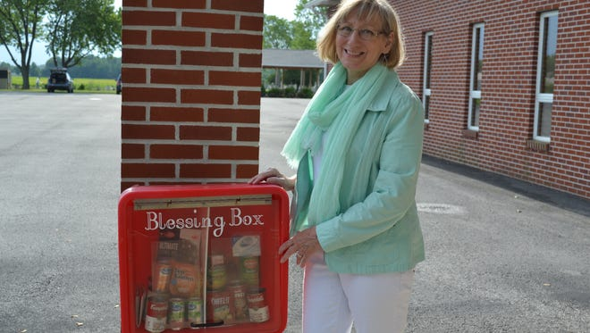 Pastor Chris Young stands beside the Blessing Box in the parking lot of St. Paul Lutheran Church. Young said she wants the Blessing Box to express to the community that the church stands with those in need.