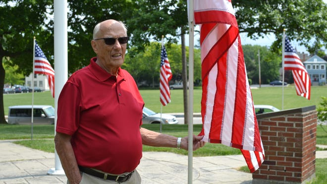 Larry Cronin stands with one of the 22 flags he cares for each summer. In addition to taking care of the physical aspects of the flag, Cronin also leads a troop of volunteers who raise the flags every morning and lower them every evening from Memorial Day through Labor Day.