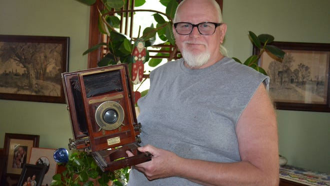 """Terry Witter displays cameras from several eras in his home, including this vintage portrait camera that was used at Fachman Studios in Port Clinton. Witter collected his favorite photos for a book, """"A Slice of My Life…The World According to Witter."""""""