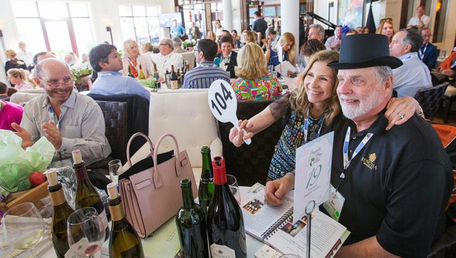 Mary Dewane and Joe Anderson celebrate making a winning bid during the 2016 Southwest Florida Wine & Food Fest auction at Miromar Lakes Beach & Golf Club.