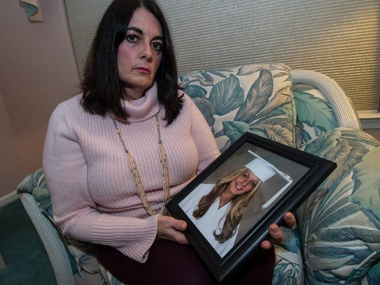 Pat Trott holds a portrait of her daughter Nicole,