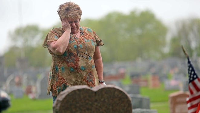 Linda Bucci grieves over the grave of her daughter Tina who found dead from an overdose last November in Claymont. Once a week she visits the grave that her daughter shares with her late husband who committed suicide.