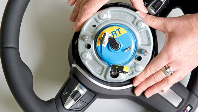A worker demonstrates a pyro-electric wheel airbag initiator during a presentation for journalists at the international automotive supplier Takata Ignition Systems in 2014