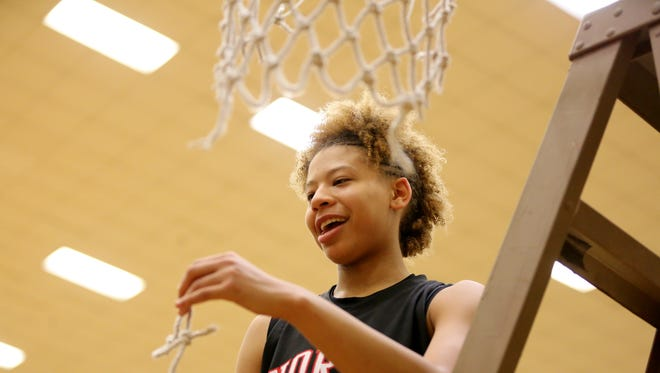 North Central sophomore Rikki Harris cuts off a piece of the net after the Panthers' sectional title win Saturday night.