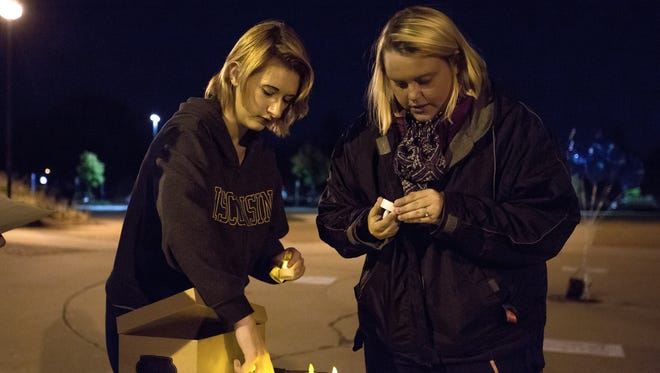 University of Wisconsin-Stevens Point students Kat Wojner, left, and Kaylee Roberts prepare candles for an event on the university's campus which was a part of the National Vigil and Day of Action for Survivors of Sexual Assault in Stevens Point, Wis., on Thursday, October 19, 2017.