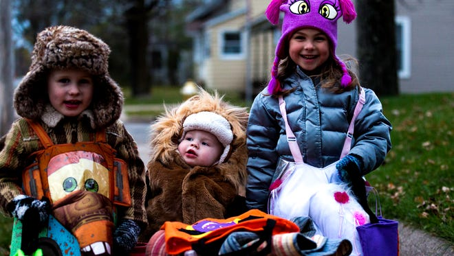 Garrison Arnat, from left, 5, Evelyn Arnat, 1, and Greyson Arnat, 4, pose for a photo while trick-or-treating in Stevens Point, Wis. on Halloween, Tuesday, October 31, 2017.