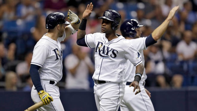 Tampa Bay Rays' Tim Beckham, center, celebrates with Shane Peterson, right, and Evan Longoria, left, after scoring on a two-run single by Peter Bourjos off Houston Astros relief pitcher Will Harris during the sixth inning of a baseball game on Saturday.