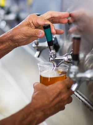 A beer is poured inside the Iowa Craft Beer tent at the Des Moines Art Festival in Western Gateway Park on Saturday, June 27, 2015.