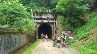 A group of cyclists stands outside Tunnel 2 on the Elroy-Sparta Trail.