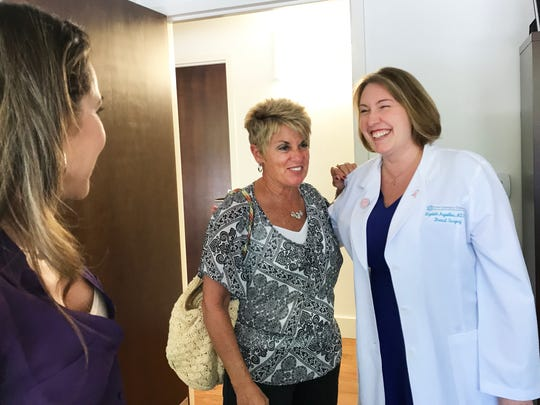 "Dr. Elizabeth Ann Arguelles, right, a certified breast surgeon with 21st Century Oncology in Naples, smiles and laughs as she talks with patients Donna Lento, 59, center, and Joanne Janopoulos, 45, who recently underwent the ""hidden scar"" approach to breast surgery."